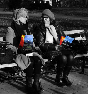 Two women with lit sitting on a bench